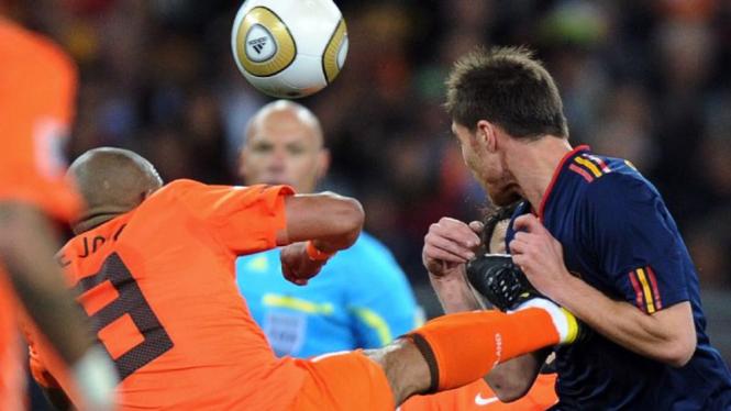 Nigel de Jong (Belanda/kiri) menendang Xabi Alonso