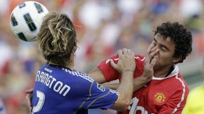 Pemain MU Fabio (kanan) berebut bola dengan Michael Harrington