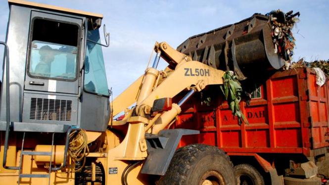 Traktor memindahkan sampah yang akan dibawa ke TPST Bantar Gebang.