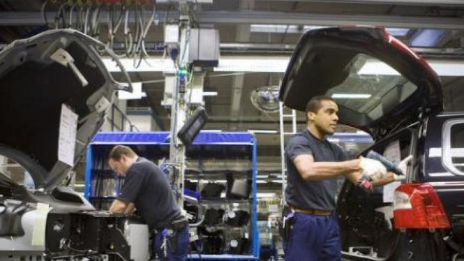 Dua pekerja menyelesaikan pembuatan mobil Volvo di Gothenburg, Swedia