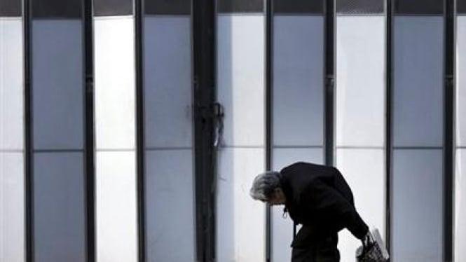 Orang tua berjalan di depan kuil di Jepang
