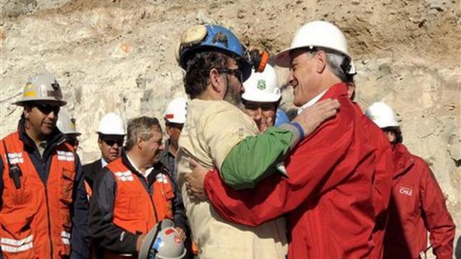 Presiden Chile, Sebastian Pinera, (kanan) memeluk seorang pekerja yang selamat