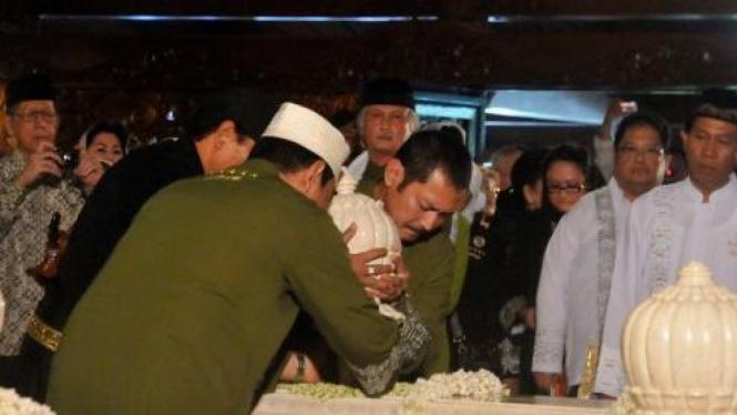 Bambang dan Tommy Soeharto (belakangi kamera) pasang mahkota nisan Soeharto