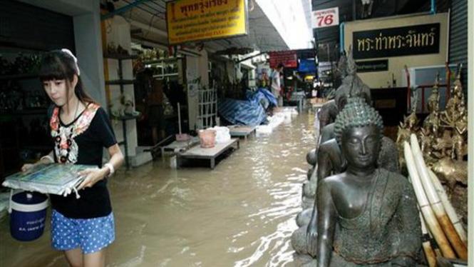 Seorang gadis Thailand melintasi gang yang tergenang banjir di Bangkok