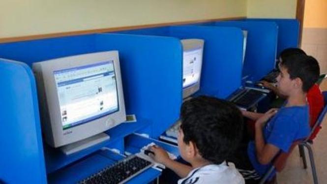 Anak-anak Palestina membuka Facebook di warung Internet