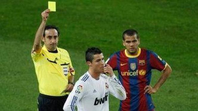 Cristiano Ronaldo (putih) menerima kartu kuning di duel el clasico