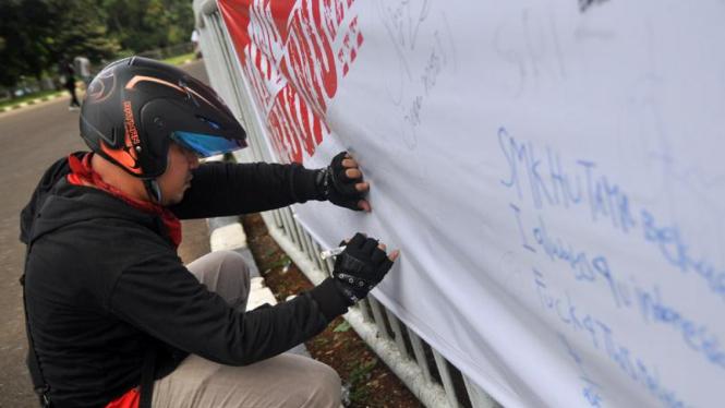 Seorang suporter menandatangani spanduk dukungan untuk Timnas di Piala AFF 2010
