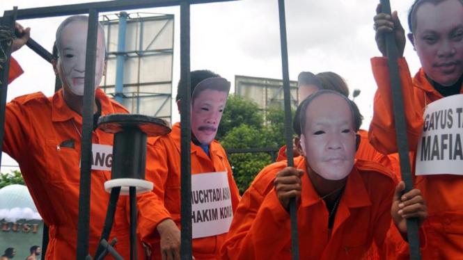 Aktivis ICW mengenakan topeng berwajah koruptor dalam unjuk rasa beberapa waktu lalu.