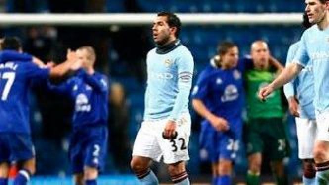 Carlos Tevez (tengah) berjalan tertunduk lesu usai timnya kalah dari Everton