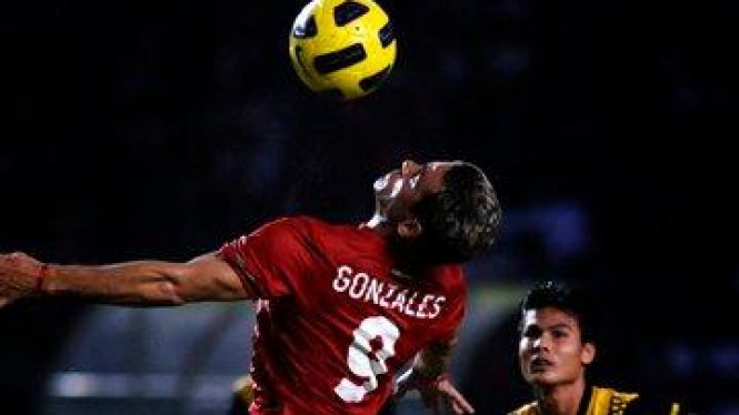 Cristian Gonzales (kiri) dijaga Mohd Muslim Ahmad