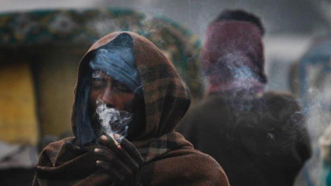 Seorang penarik becak menghisap rokok di tengah dinginnya cuaca India