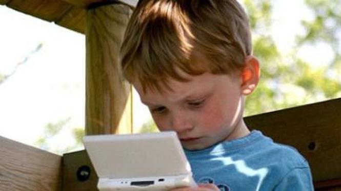 Seorang anak yang tengah asyik bermain game