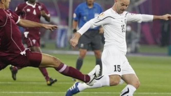 Striker Uzbekistan Alexander Geynrikh (putih) dikawal pemain Qatar Ibrahim Majed