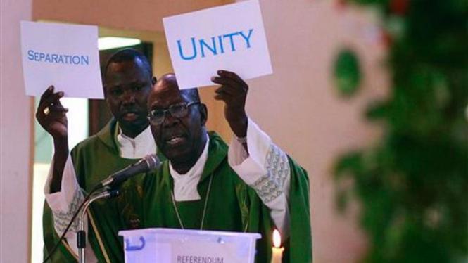 Seorang rohaniwan di Sudan memperlihatkan kotak suara tiruan