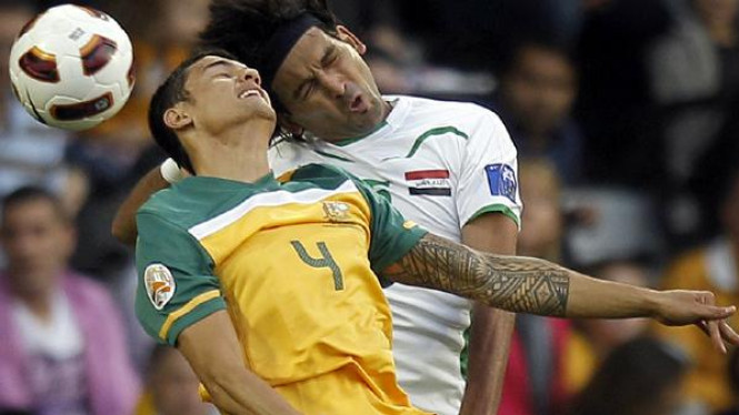 Tim Cahill (Australia/kiri) berebut bola dengan Hadi Aghili (Irak)