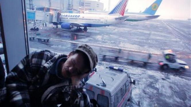 Seorang calon penumpang tidur pulas di Bandara Domodedovo, Moskow
