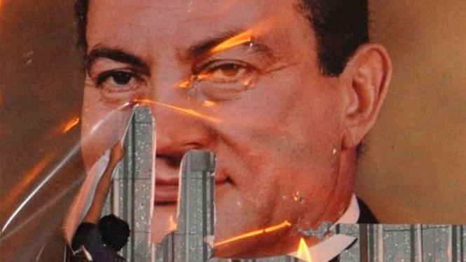 Seorang demonstran di Alexandria merusak poster Presiden Mesir, Hosni Mubarak