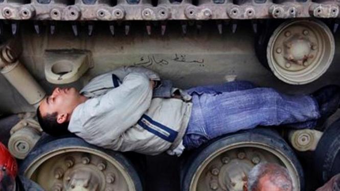 Seorang demonstran di Kairo, Mesir, tidur di roda-roda tank