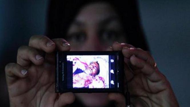 Seorang aktivis di Bahrain memperlihatkan foto demonstran yang terluka