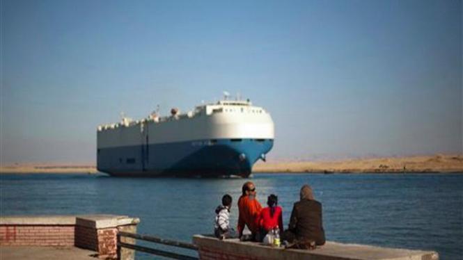 Warga Mesir menyaksikan suatu kapal kargo melintas Terusan Suez