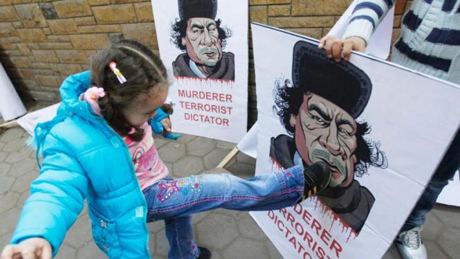 Seorang anak di Libya menendang poster bergambar Moammar Khadafi