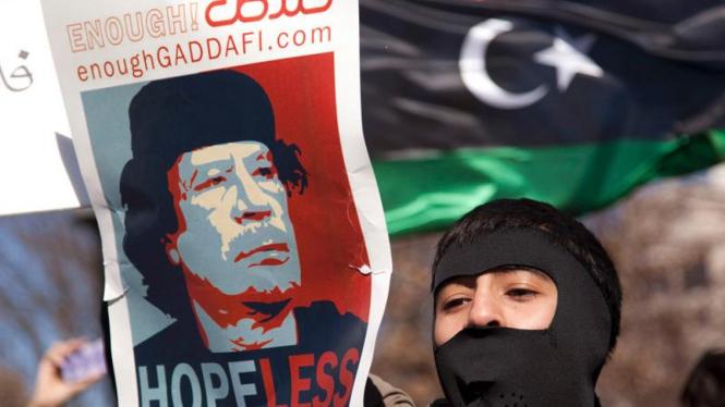 Demonstran membawa poster anti pemimpin Libya Moammar Khadafi