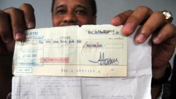 Rahman Halid, menunjukkan cek kosong atas nama Ilham Arief Sirajuddin