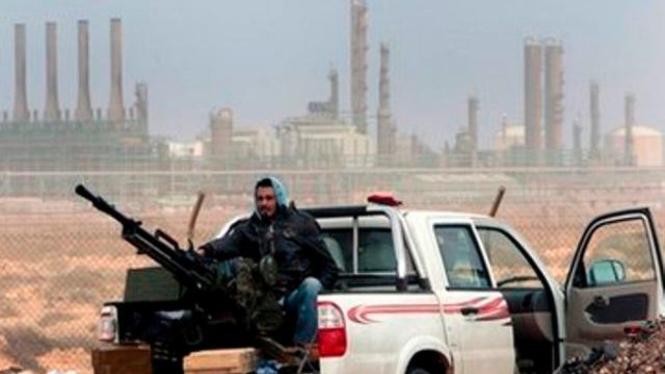 Seorang tentara anti rezim Khadafi berjaga di depan ladang minyak Libya