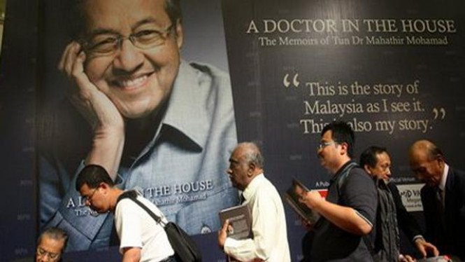 Mahathir Mohamad (kiri) memberi tandatangan atas otobiografi terbaru