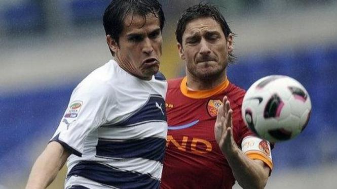 Francesco Totti (kanan) berebut bola dengan Christian Ledesma