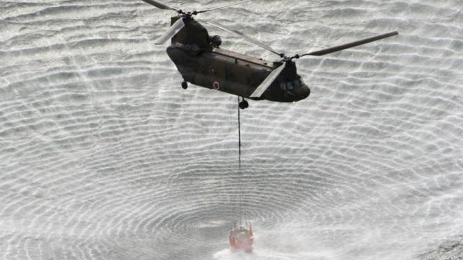 Helikopter Militer Jepang mengambil air untuk mendinginkan PLTN Fukushima.