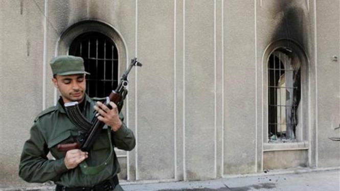 Tentara Suriah berjaga di bangunan yang dibakar massa di Kota Daraa, Maret 2011