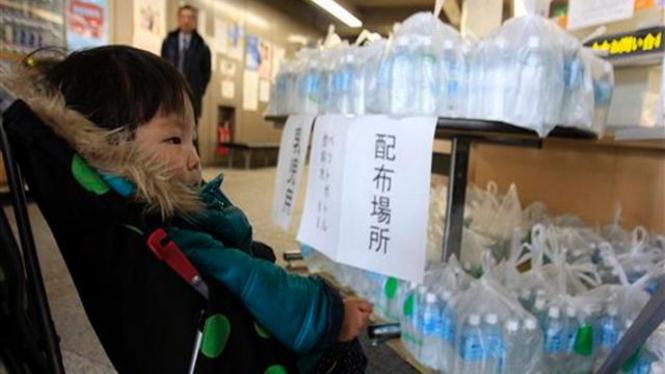 Seorang bocah di Tokyo menunggu ibunya mendapatkan air minum kemasan