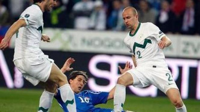 Gelandang Italia Riccardo Montolivo dihadang dua pemain Slovenia