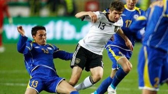 Thomas Mueller (Jerman/13) diapit pemain Kazakhstan