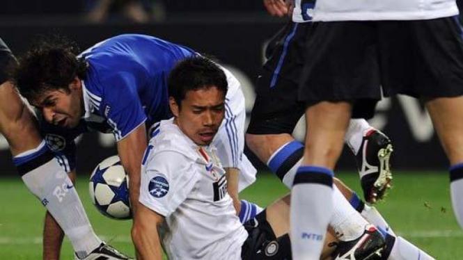 Yuto Nagatomo (putih) menghadang laju Raul Gonzalez