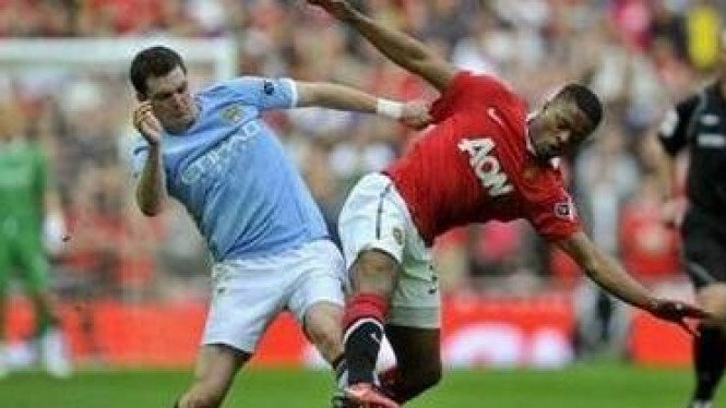 Pemain Man City Adam Johnson (biru) dan Patrice Evra