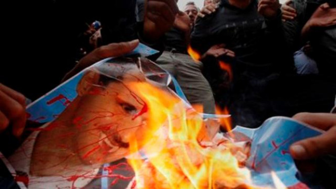 Demonstran di Siprus membakar poster Presiden Suriah, Bashar Assad