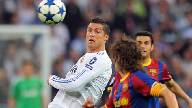 Cristiano Ronaldo (kiri) dibayangi Carles Puyol