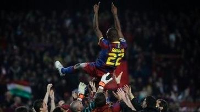 Eric Abidal (atas) diarak pemain Barcelona