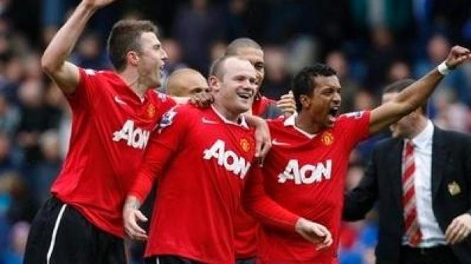 Pemain MU merayakan gol Wayne Rooney (tengah)