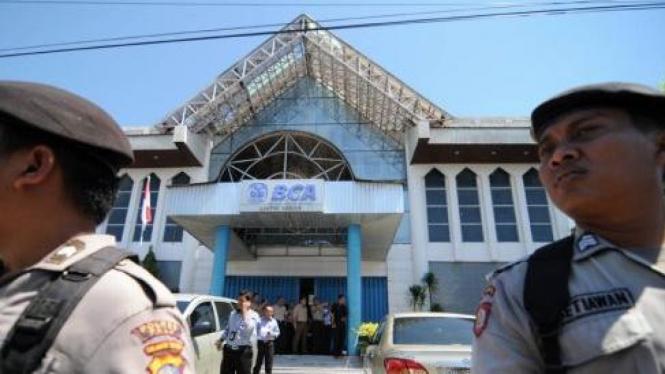 Polisi berjaga di Bank BCA Palu tempat dua polisi tewas ditembak 25 Mei 2011