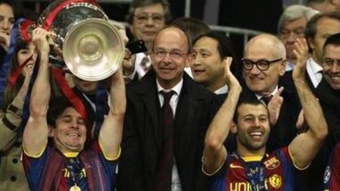 Lionel Messi (kiri) dengan trophy Liga Champions 2011