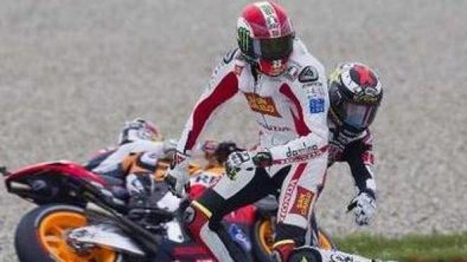 Marco Simoncelli (putih) terlibat kecelakaan dengan Jorge Lorenzo