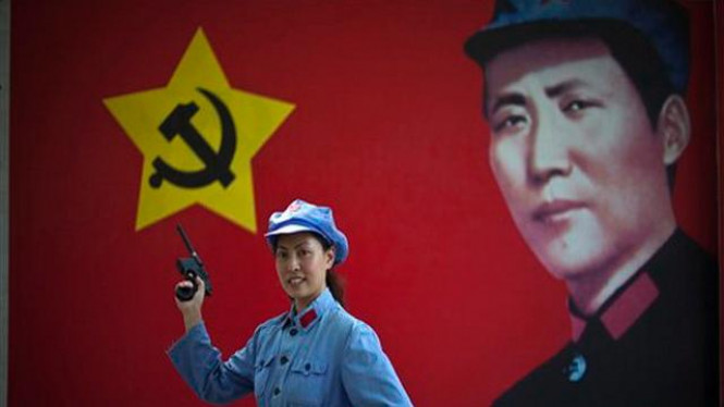 Seorang turis berpose sebagai Tentara Merah di Yang'an, China