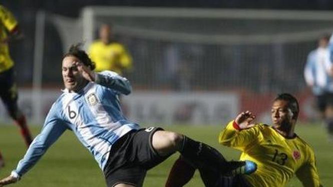Pemain Argentina Gabriel Milito (biru-putih) dan pemain Kolombia Freddy Guarin