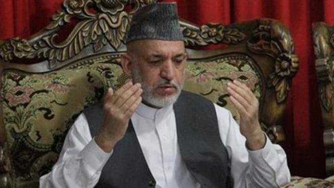 Hamid Karzai berdoa pada pemakaman adiknya.