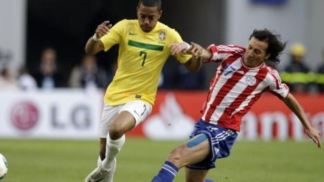 Pemain Brasil Robinho (kuning) dan pemain Paraguay