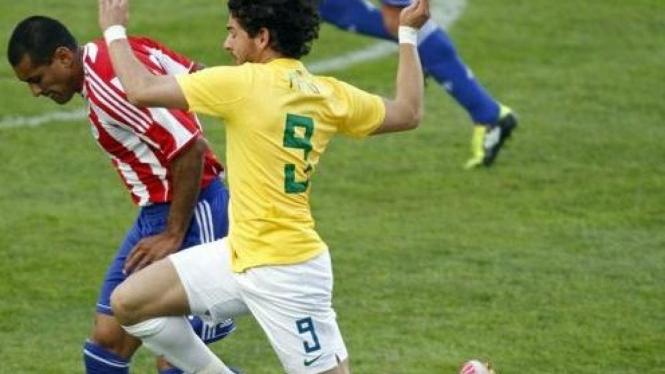 Pemain Brasil Pato (kuning) diapit pemain Paraguay