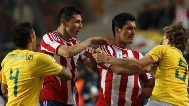 Pemain Brasil (kuning) dengan pemain Paraguay